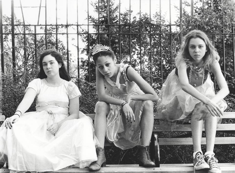 Black and white photo of three young women sitting on a bench wearing formal dresses